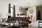 Minibar auf Couchtisch und braunes Sofa vor Essplatz in offenem Wohnraum in klassisch modernem Stil