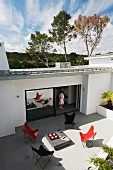 Butterfly armchairs in various colours on large terrace of modern house with woman standing in open terrace door
