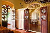 Bedroom with open terrace door; wooden partition wall with carved arch and open double doors showing view of adjacent room