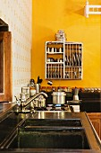 Kitchen counter with vintage tap fittings over sink and crockery in drying rack hung on yellow wall