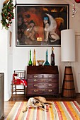 Festively decorated hallway with painting above coloured bottles on antique bureau; dog on striped rug