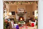 Adventlich dekoriertes Wohnzimmer mit verschiedenen Polstersesseln und brennendem Kaminfeuer