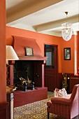 Apricotfarbene Eingangshalle eines Landhauses mit antiken Bodenfliesen und einem rot lackierten, offenen Kamin; an der Decke eine Lampe aus geschliffenem Glas
