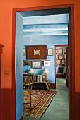 Blick durch roten Türrahmen in pastellblaues Arbeitszimmer mit pastellblau übertünchten Holzbalken und orientalischem Teppich