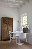 Simple chair and modern shell chairs at a white table in front of a rustic farmhouse cupboard