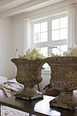 Antique plant pots made of weathered stone on a modern coffee table in a living room with a traditional feel