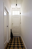 Narrow hallway with checkerboard pattern floor in a simple town home