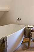 Modern bathtub with a wall mount tub faucet and wooden stool
