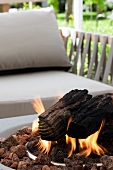 Modern outdoor fire pit with burning logs in front of an upholstered chair