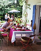 Garden terrace with terra cotta tiles, open French doors with blue shutters and a table set for a party