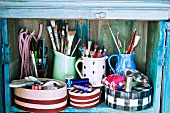 Assorted sewing and craft supplies in an old wooden cupboard