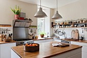 Spacious kitchen with open shelving and solid oak work surfaces. The pendant lights and units are both by Ikea