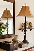 Old wooden jewellery box and silver urn on surface with ornate brass lamp stand. A rectangular wooden framed mirror hangs on the wall