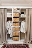 Offener Kleiderschrank mit Aufbewahrungskörben und bodenlangen Vorhängen