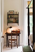 Art deco gooseneck desk lamp on small wooden reading table in bedroom with four poster bed and footstool