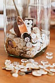 Buttons in and around a glass jar.