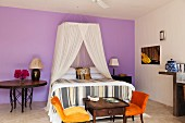Double bed with net canopy and orange velvet chairs in lilac walled bedroom
