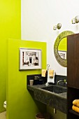 Black stucco sink and countertop in bathroom with lime green walls