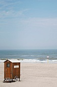 Wooden changing room on a lonely stretch of sandy beach