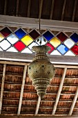 Indian-style metal pendant lamp hanging from wooden ceiling with stained glass ribbon window