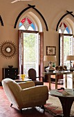 Indian residential house - upholstered armchair on red tiled floor in elegant living room with open terrace doors and coloured fanlights in pointed arches above