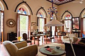 Indian residential house - elegant living room with modern standard lamp in lounge area, open terrace doors and coloured fanlights in pointed arches above