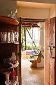Eckregal mit Gläsern neben offener Tür und Blick durch Wohnraum eines indischen Wohnhauses in den Garten