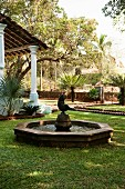 Fountain with statue in garden of Indian residential house with colonial-style porch on pillars