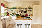 Barstools and a butchers island in a white kitchen with colourful crockery