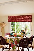 Breakfast table with patchwork tablecloth made from assorted Kathryn Ireland fabrics beneath window with Kathryn Ireland Sandeep blind fabric