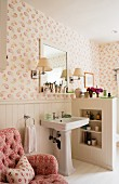 Pink button tufted armchair in bathroom with dado wood panelling and Kathryn Ireland Quilt wallpaper