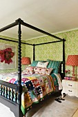 Patchwork quilt and cushions by Kathryn Ireland on fourposter bed in bedroom with green patterned wallpaper and orange print lampshades