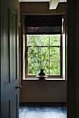 Offenstehende schlichte Kassettentür mit englischem Türknauf; Blick in Vorraum auf Sprossenfenster mit Faltrollo