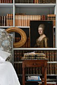 Oil portrait of lady in front of simple shelving holding antiquarian book volumes