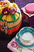 Crocheted tea cosy next to teacup with gilt pattern and tea caddy