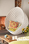 White hanging chair with scatter cushions