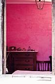 Antike Holzkommode mit Marmorplatte an pinkfarbener Schlafzimmerwand
