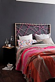 Artistic atmosphere in modern bedroom - bed with headboard made from colourful cords against black-painted wall