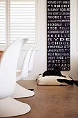 White, plastic shell chairs in front of window with closed interior shutters and blackboard with lettering on wall