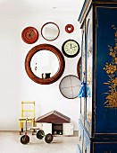 Vintage-style child's bedroom - tricycle and small chair against wall below circular mirrors and wall clock with painted wardrobe to one side