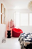 Red upholstered armchair next to stylised tree used as clothes rack in corner of white bedroom with white interior window shutters