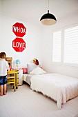 Weisses Kinderzimmer - Bett mit Flokati Tagesdecke am Fenster und kleiner Junge vor Tisch mit Ritterburg