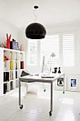 Mobile desk under black pendant lamp in modern interior