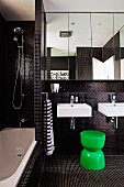 Modern bathroom with black mosaic tiles and green plastic stool in front of twin washbasins below mirrored cabinet