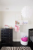 Nursery in black and white - modern pendant lamp above zebra-patterned rug and black vintage chest of drawers