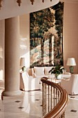 Curved wooden balustrade and massive stone columns in front of sumptuous tapestry in lobby of historical hotel