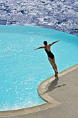 Curved, electric blue infinity pool next to dark blue ocean; woman in process of diving from pool edge