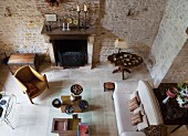 Top view of rustic living room with exposed stone walls and lounge area in front of open fireplace