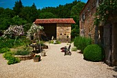 Simple country house and barn in open Mediterranean garden with seating area on gravel terrace