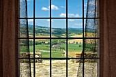 View of Tuscan landscape through window lattice